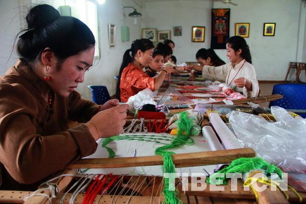 10余位女孩正在绣制一幅宽超过5米、长超过10米的巨型刺绣唐卡。摄影:刘莉