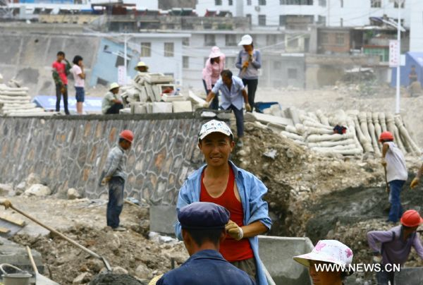 A worker is seen grinning at a building site in Zhouqu County of Gannan Tibetan Autonomous Prefecture, northwest China's Gansu Province, Aug. 2, 2011. After a year's recovery from the deadly mudslide which occurred on Aug. 8, 2010, the beautiful county of Zhouqu has resumed hustle and bustle as the life goes on the way it did. [Photo/Xinhua]