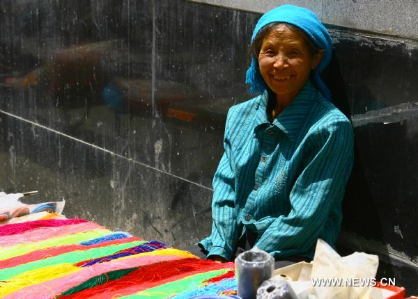 A vendor selling yarn simles at the camera in Zhouqu County of Gannan Tibetan Autonomous Prefecture, northwest China's Gansu Province, Aug. 2, 2011. After a year's recovery from the deadly mudslide which occurred on Aug. 8, 2010, the beautiful county of Zhouqu has resumed hustle and bustle as the life goes on the way it did. [Photo/Xinhua]