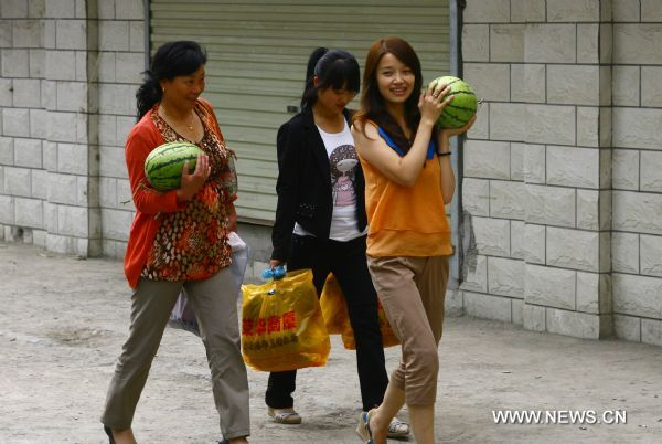 Women carry watermelons in Zhouqu County of Gannan Tibetan Autonomous Prefecture, northwest China's Gansu Province, Aug. 2, 2011. After a year's recovery from the deadly mudslide which occurred on Aug. 8, 2010, the beautiful county of Zhouqu has resumed hustle and bustle as the life goes on the way it did. [Photo/Xinhua]