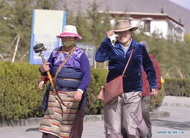 Tibetan Buddhist believers walk around Potala Palace for praying in Lhasa