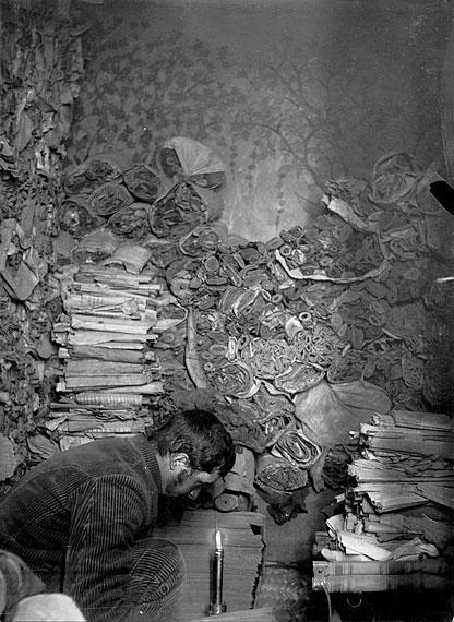 斯坦因 徐文堪/伯希和在敦煌莫高窟藏经洞内拣选文书。