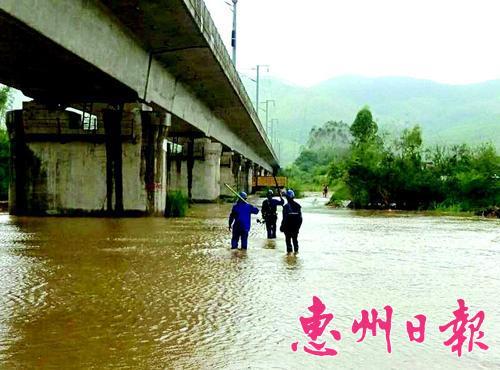 """▲道路因台风""""妮妲""""被淹没,供电工作人员涉水背工具赶抢修。"""