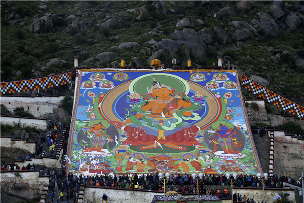 Thangka adorns hillside during Shoton