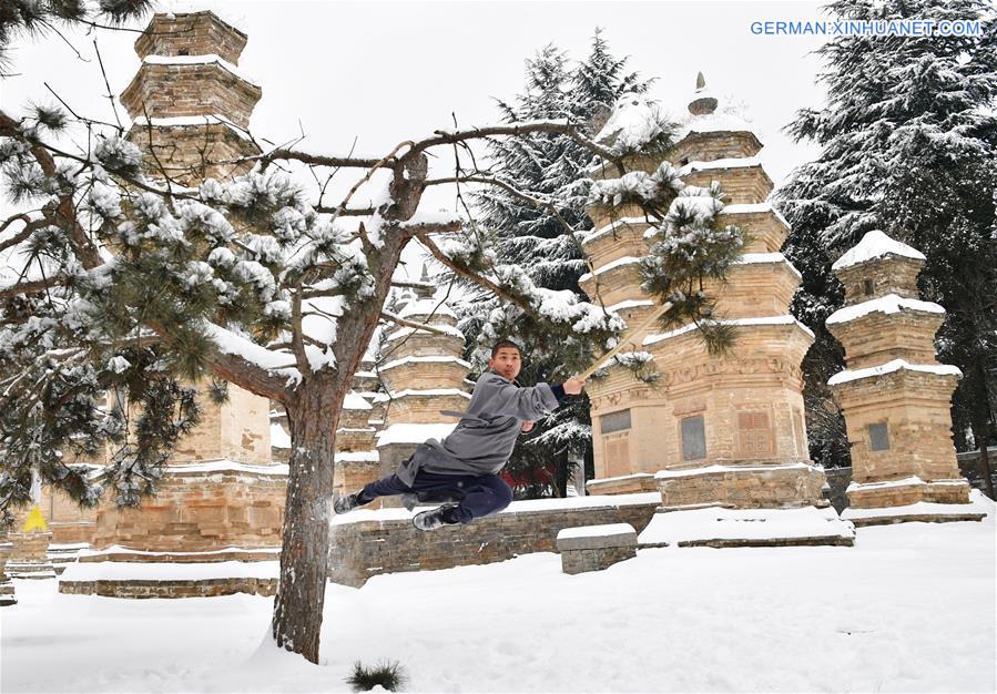Mönche üben Kampfkünste im schneebedeckten Pagodenwald des Shaolin-Tempels