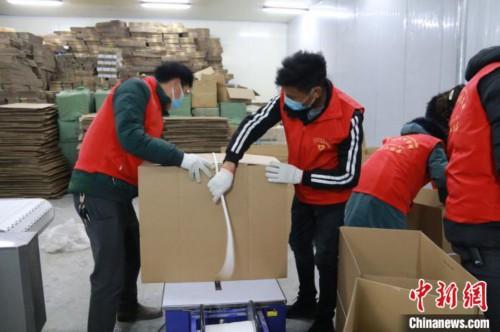 圖為志愿者正在制作包裝箱。蔡堯 攝