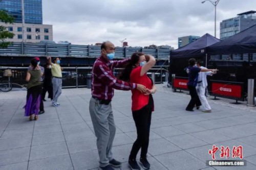 资料图:当地时间8月16日,居民戴着口罩在纽约法拉盛社区广场跳舞。<a target='_blank' href='http://www.chinanews.com/' _fcksavedurl='http://www.chinanews.com/'><p  align=